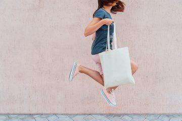 Frau mit Beutel hüpft hoch